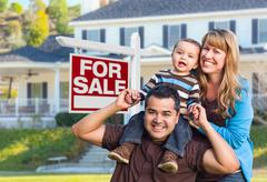 Young Family in Front of For Sale Sign and House Stock Photos