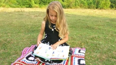 Girl turns book page. Stock Footage