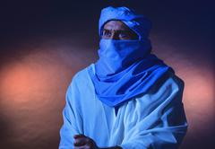 Berber man in night light wearing blue turban with white robe. Leaning on can Stock Photos