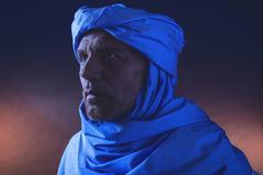 Berber man in night light wearing blue turban with white robe. Studio shot. Stock Photos