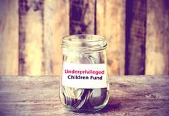 Coins in glass money jar with Fund for Underprivileged Children fund Stock Photos