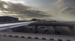 Airplane driving over bridge with cars in traffic below Stock Footage