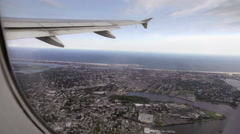 Airplane passenger seat window view of wing flying over New York during day Stock Footage