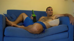Topless man lying on couch, drinking beer and watching tv Stock Footage
