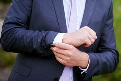 Man in black jacket wears cuffs in park Stock Photos