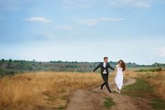 Groom catches bride on the summer field Stock Photos
