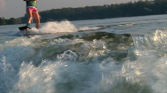 Red head teen girl riding wakeboard on sunset Stock Footage