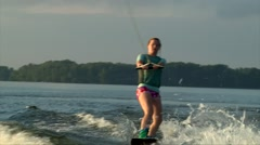 Slim teenage girl on wakeboard, sunset sky Stock Footage