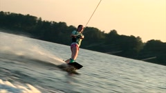 Teen girl on wakeboard make wake to wake ricky trick Stock Footage