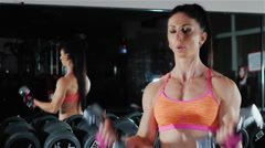 Athletic woman trains muscles of the hands. Female bodybuilding Stock Footage