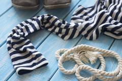 Frock and rope on a blue shabby wooden table. Stock Photos
