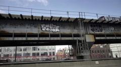 Slow motion panning shot of graffiti on Williamsburg Bridge cars passing NYC Stock Footage