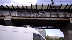 Shaky footage of graffiti on bridge overhead with white van driving below in NYC Stock Footage
