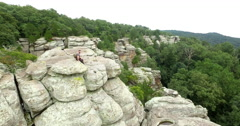 Man Sitting on Rock Boulder from Aerial Perspective Stock Footage