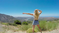 Young beautiful woman on a background of mountains. 4K 30fps ProRes (HQ) Stock Footage