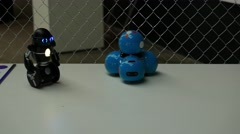 Two small toy robos on a table Stock Footage