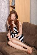 Candid portrait of thoughtful young beautiful redhead woman sitting on sofa Stock Photos