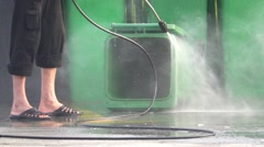 Slow motion cleaner cleans plastic dumpster with water Stock Footage