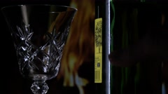 White Wine being poured into a crystal glass in front of  log fire Stock Footage