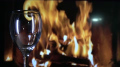 Red wine being poured into a glass in front of a roaring log fire Stock Footage
