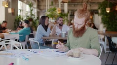 Ginger man working in cafe, on table graph and papper. Behind him cheerful group Stock Footage