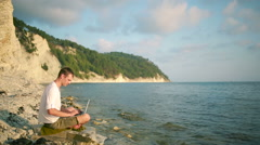 Happy man with modern laptop sitting on the beach. remote work Stock Footage