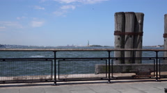 Statue of Liberty in background at fence of waters edge 4k Stock Footage