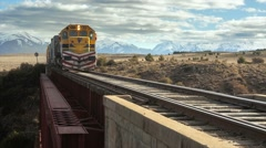 Train crossing passing old bridge over the river scenic mountains nature Stock Footage