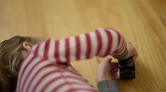 Sleepy Child In Christmas Pajamas, Plays With Toy Train On Floor Stock Footage