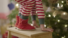 Closeup Of Child Climbing Up Step Stool Next To Christmas Tree, To Help Decorate Stock Footage