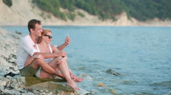 Couple in love on the beach. make a video call on your smartphone Stock Footage
