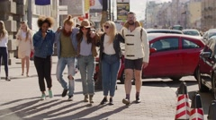 Frontal view of a group of teen hipster friends enjoying a walk on the street Stock Footage