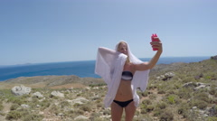 Girl blonde in swimsuit posing near the sea makes selfie phone. Stock Footage