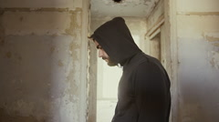 Hooded young man inside destroyed abandoned building,slow motion,dramatic Stock Footage