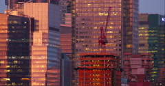 Group of skyscrapers and crane atop a construction site Stock Footage