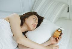 Young attractive Japanese woman sleeping in bed Stock Photos
