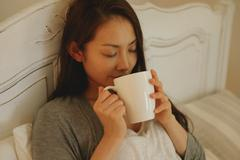Young attractive Japanese woman drinking coffee in bed Stock Photos