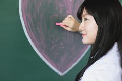 Japanese high-school student writing on classroom blackboard Kuvituskuvat