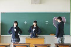 Japanese high-school students in front of classroom blackboard Kuvituskuvat