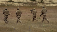 Soldiers shoot and run in the field Stock Footage