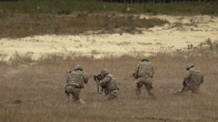 Many soldiers shoot in the field Stock Footage