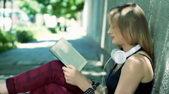 Punk girl sitting on the pathway and reading interesting book Stock Footage