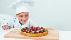 Close up portrait young chef baker examines chocolate cake with sweets Stock Footage