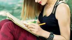 Angry, punk girl sitting on pathway and crossing something out from notebook Stock Footage
