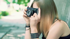 Punk girl sitting on the pathway and doing photos on old camera, steadycam shot Stock Footage