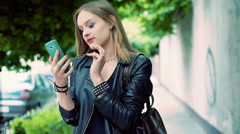 Punk girl texting on smartphone while standing on pathway and smiling to the cam Arkistovideo