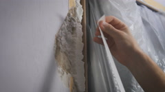 Worker protecting batten moulding with masking tape before painting at home Stock Footage