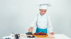 Young chef baker decorating chocolate cake using greenery sweets and fruits Stock Footage