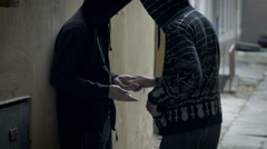 Masked bandit handing over the narcotics to a drug addict Stock Footage