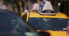 Parked yellow taxi cab as pedestrians cross by in slow motion Stock Footage